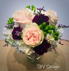 Bridal bouquet including pink garden roses, lime green berries, and eggplant carnations.