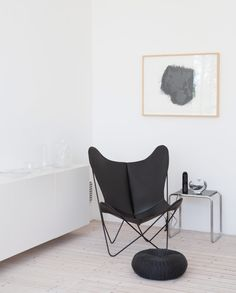 Bright and minimalistic home of Ingegerd Råman. One of the all redesigned models of the bat chair. The small table; Bauhaus, design by Marcel Breuer, and the Pouffe from Ikea - Sköna hem, Sweden.
