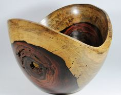This beautiful bowl is made of Cocobolo and has a unique shape and dark colors. Cocobolo is one of the most unique and exotic tropical hard woods. Colors can vary from bright oranges, all shades of reds, to deep dark browns. This bowl meassures 9 x 8 x 6.5h Each piece is made by our artists first selecting the most interesting pieces of wood for our collection. The woods are then cut appropriately, but the natural shape of the piece is what dictates the final design that is made. The…