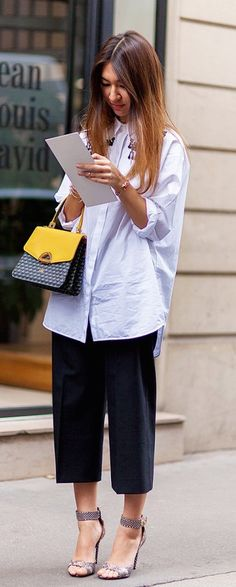 Short tailored culottes are totally in, especially with an oversized shirt and colorful purse