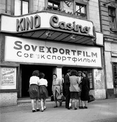 """David """"Chim"""" SEYMOUR :: People standing outside a movie house which plays Russian language films for the Soviet soldiers / Berlin, 1947"""