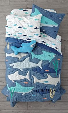 Shop Shark Bait Bedding. This shark bedding is positively brimming with every kind of shark imaginable. The quilt features a dark blue base with plenty of appliqued ocean-themed accents. #Kidsroomsdecor