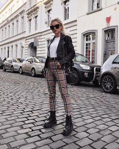 30 looks para quem ama calça xadrez - Guita Moda. Jaqueta de couro, blusa branca, calça bege, coturno preto.