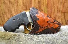 This is a hand tooled vegetable tanned leather holster for a small revolver with a 2 barrel. It has a traditional oak leave design tooled on