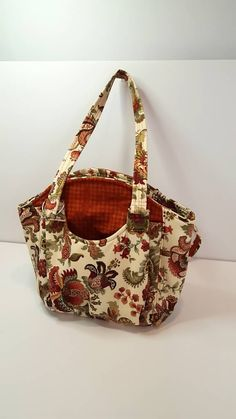 "Approximately 12"" by 12"" purse with two pockets on the outside, pockets on the inside with one zipper pocket on the inside, shoulder straps approximate 30"". More"