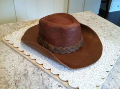 Cowboy Hat - This cake was made for my father-in-law; Brim was made using a 1:1 mixture of fondant & gumpaste, rolled out and cut using a template from a real hat, which I then turned upside down and placed cut brim over (plastic wrap covering real hat to protect it) and let it dry for a couple days. The platic wrap created some very cool (unintentional) ridges within the brim that made it look weather, just like real leather. The hat portion was a 3 layer yellow cake, filled with chocolate…