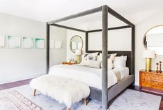 Feminine canopy bed with furry bench and small artwork on walls