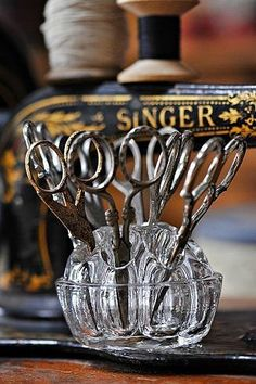 I ❤ sewing . . . Antique Scissors diplayed in a floral frog.  In background antique Singer sewing machine displayed.