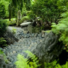 """Here, tumbled gray river rocks of uniform size have been carefully arranged in this meandering dry streambed to create the illusion of flowing water. Ferns and evergreens line the stream, softening its """"shoreline. Garden Rake, Diy Garden, Dream Garden, Shade Garden, Garden Landscaping, Zen Rock Garden, Buddha Garden, Japanese Garden Landscape, Small Japanese Garden"""