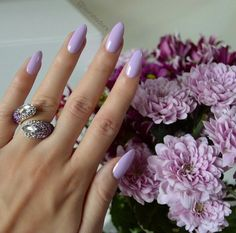 Purple nail polish, long nails. Purple flowers in the background.