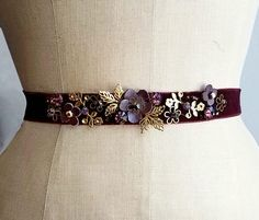 Burgundy velvet ribbon, lined with black grosgrain ribbon, embroidered with hand-cut leather flowers, gold metal filagree embellishments, Czech crystals jewels in dark amethyst, opal and gold finishes. Can be worn as belt, choker, necklace, multiple possibilities.