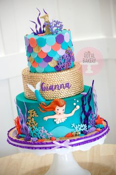 Vintage mermaid cake with underwater scene, swimming mermaid and scales. The middle tier is gold sequins.