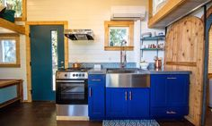 A galley kitchen with a four-burner stove, range hood, oven, full-sized sink, and full-sized fridge with freezer is located in the center of the home opposite the large window.