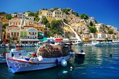 Buildings along the azure shoreline, painted in the most vivid shades, with the most beautiful sights of the Aegean Sea.