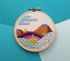 Hand stitched embroidery of a fantastical landscape of rolling hills, mountains, and plant life. Made with DMC embroidery floss in a 4 inch bamboo hoop, which serves as a frame.