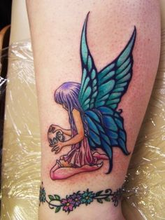 Small fairy with blue and green wings holding a skull tattoo, cute.