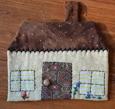 This sweet decorative tea time pot holder is a little brown cottage with a button door knob and the chimney doubles as a hanging loop.  My mom (dont tell her I told you this!) is 81 years old and has been sewing since she was 10! She so enjoyed choosing the calico fabrics for these sweet potholders and embroidering each with its own unique flower garden.  She hand appliqued the windows and door, then finished each pot holder with embroidery trim, flowers and a cute little button door knob…