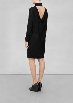 & Other Stories   Merino Wool Dress. A warm and cozy merino wool dress featuring a draped cut-out in the back, a slightly higher collar and a straight fit.