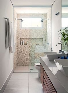 banheiro com lavabos e chuveiros duplos