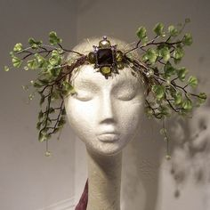 One of a kind, delicate tender ferns and pale green sparkling beads are wound into a wired base wrapped in brown ribbon and mossy soft yarns. The ribbon unties in back, so this crown will fit any fairy's head. The beautiful green glass brooch in the center of the crown is removable if you wish.