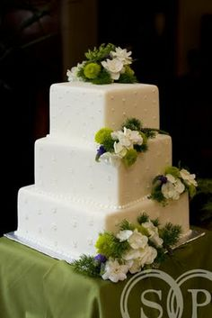 White square wedding cake with white, green, and blue fresh floral accents.