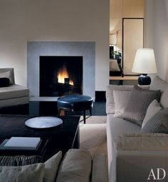 Armani's Central Park West pied-à-terre was renovated with the help of Thomas O'Brien of Aero Studios. The living room of the penthouse space displays several Armani/Casa designs, including the sofa, silk-upholstered slipper chair, and bronze table lamp.
