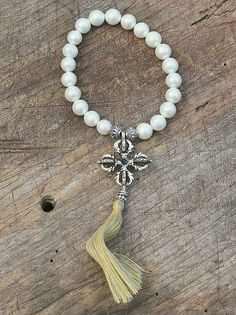 Frosted shell pearl wrist mala bracelet decorated with a Nepalese dorje (vajra) pendant