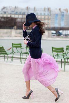 pink skirt, navy cardigan and hat. Gray heels.