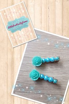A pair of 45mm silver crocodile hair clips hand decorated with a teal blue rose embellishment with 3 blue heart shaped pearls and then a