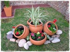 Flower pots and rocks make a cute addition to your outside landscaping. diy garden landscaping 15 One-Day Garden Projects Anyone Can Do Garden Yard Ideas, Garden Landscaping, Rocks In Landscaping, Simple Backyard Ideas, Diy Garden Ideas On A Budget, Diy Landscaping Ideas, Creative Garden Ideas, Cheap Garden Ideas, Mulch Ideas