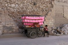 Al-Bab, Syria  A child eats candy floss while selling it on a street cart
