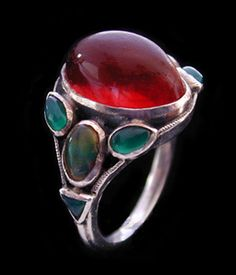 This is not contemporary - image from a gallery of vintage and/or antique objects. SIBYL DUNLOP (1889-1968)  A silver ring with a central cabochon fire opal and with opal and chrysoprase  set to shoulders.