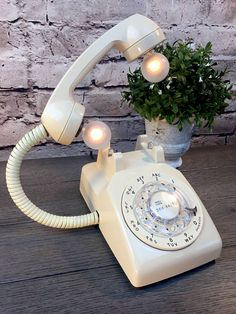 This is a vintage rotary phone upcycled into unique lighting. Weve scrubbed and cleaned it to make room for new lighting elements that give this old phone a new life suitable for any type of decor. The hand set has two UL rated 7 watt candelabra bulbs supported by flexible lamp pipe