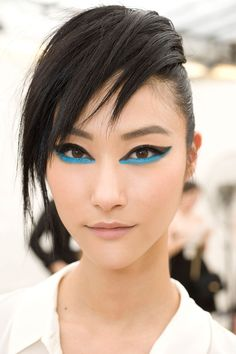 Chanel, Resort 2014 runway makeup. Graphic winged eyes. Black eyeliner on the eyelid with blue eyeliner underline: Chanel Stylo Yeux Waterproof Long-Lasting Eyeliner in Noir Intense and True Blue. Modern Cleopatra eye makeup. Photo: Chanel. #Chanel_runway_makeup_2014 #blue_eyeliner_makeup