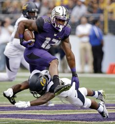 Washington tailback Dwayne Washington (12) leaps over California safety Damariay Drew during the first half an NCAA college football game Saturday, Sept. 26, 2015, in Seattle. (AP Photo/Elaine Thompson)