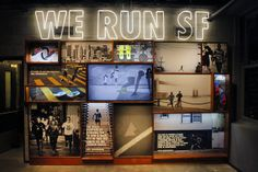 "Niketown, ""WE RUN SF"" - display wall, images in recylced bleacher framing, LCD in center panel"