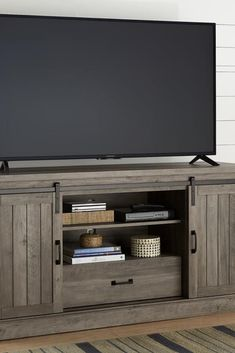 """This stylish 60"""", washed gray TV stand includes sliding barn doors and adjustable shelves, allowing you to arrange all your digital equipment in style. #lowes #cybermonday"""