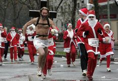 "Runners, dressed as Santa Claus, one of them carrying a cross on his shoulders to resemble Jesus Christ, take part of the ""Christmas Corrida Race"" in the streets of Issy Les Moulineaux, west outskirts of Paris, Sunday, Dec. 14, 2008. (AP Photo / Francois Mori) #"
