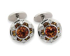 A PAIR OF 18 CARAT WHITE GOLD CITRINE AND DIAMOND CUFFLINKS, BY WILLIAM & SON Each composed of a circular panel set with a central circular-cut citrine within a calibré citrine and square scissor-cut diamond surround, to a stepped polished gold border, with angled bar link connection to an opposing matt gold oval panel, London hallmarks for 18ct gold, 2003