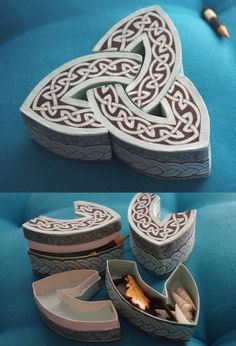 A set of three boxes, which forms a triquetra when put together. Each box is 4cm tall, and around 9cm in its longest part. Cardboard, paper and blue kraft paper. Black and silver pens for the decor...