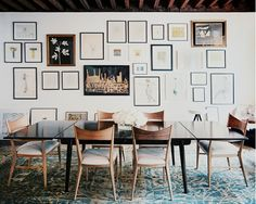 Wide gallery wall in dining room with modern table and chairs and teal rug