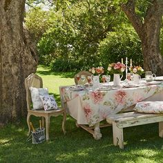 Set a Provençal-style painted table under the trees, along with can dining chairs and a rustic bench, and use crisp ticking and floral linen as tablecloths with rose-patterned accessories