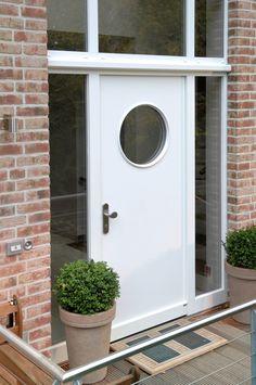 Eine ganz einfache und schlichte Holzhaustür in weiß. Umschmückt von einem Oberlicht, 2 Seitenteilen und einem Bullauge. Diese lassen den fensterlosen Flur trotzdem erhellen!