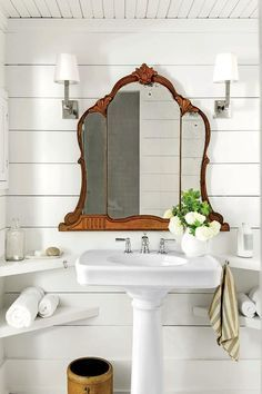 Charming shiplap bathroom with shaded sconces, vintage tri-fold mirror and…