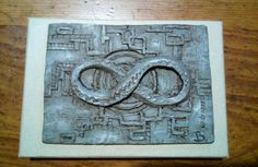 Medalla con símbolo del infinito en resina y con efecto metal envejecido