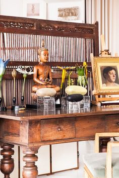 an indonesian screen ornamental flowers from belgium and a thai buddha set the tone near the entry to vicentes apartment