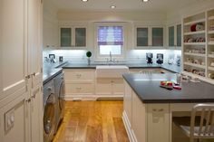 Traditional Laundry Room by Hull Forest Products. Peninsula for sewing, wrapping paper mounted in cutters, open shelves for supplies