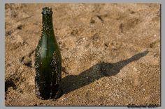 -Strijklicht- Je kunt goed in het zand het oppervlak van de fles zien.