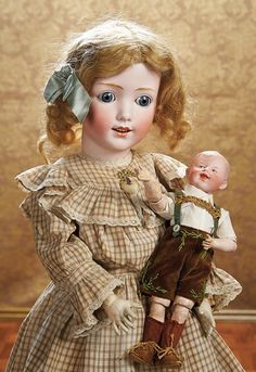 "27"" German bisque child marketed as ""Dolly Dimple"" by Gebrüder Heubach, circa 1915, marked 13 Heubach (sunburst); holding an 11"" German bisque character, also by Gebrüder Heubach, circa 1912, marked 7911 Heubach (square) Germany 0."