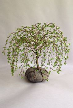 Weeping Willow Tree Sculpture  Foliage: Czech glass light green seedbeads Wire: Brown Base: Stone Size: 6 inch high by 6 inches wide    Tree Sculptures  Elegantly handmade tree sculptures are skillfully, beaded by hand and weaved together to form a tree with unique character, with twisted roots that encircle and anchor the tree to a stone foundation. Trees are created using glass seedbeads and wire. To preserve surfaces the underside of the stone foundation is covered with a protective…